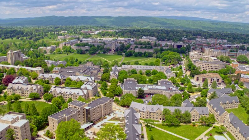 aerial view of Virginia Tech drillfield and surrounding buildings on a sunny day. Green mountains and horizon are in the background.